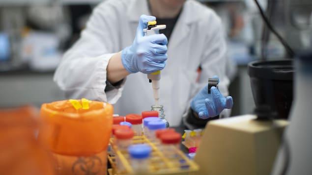Un homme portant une blouse blanche et des gants de protection dans un laboratoire.