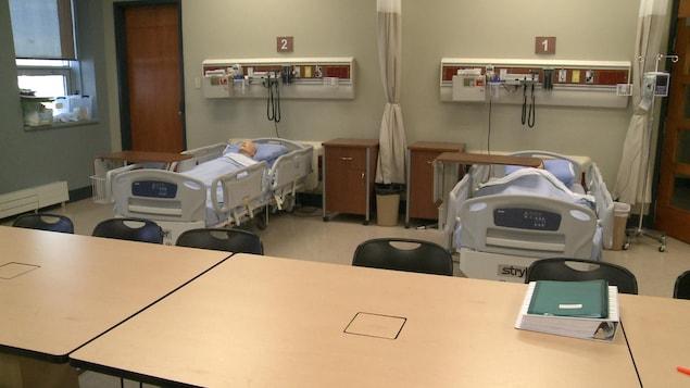 Deux mannequins sont installés dans deux lits d'hôpital dans une salle de classe.
