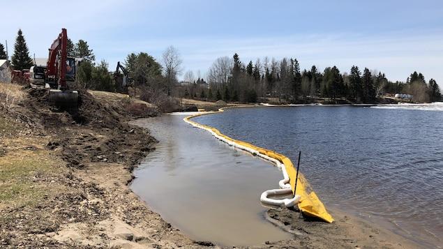 Une pelle mécanique creuse près d'un lac.
