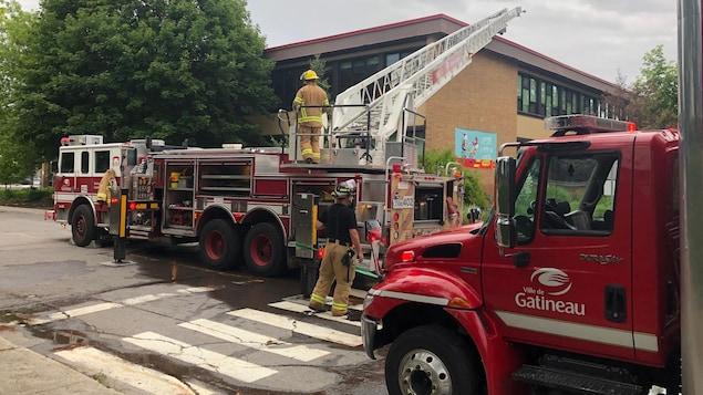 Des pompiers éteignent le feu qui a pris dans l'enceinte de l'école du Lac-des-Fées.
