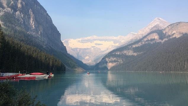 Vue du lac Louise bleu turquoise, encadré par les montagnes recouvertes de neige. À gauche, des canots sont arrimés au quai.