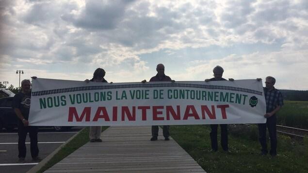 Des citoyens de Lac-Mégantic tiennent une pancarte qui réclame une voie de contournement le plus rapidement possible.