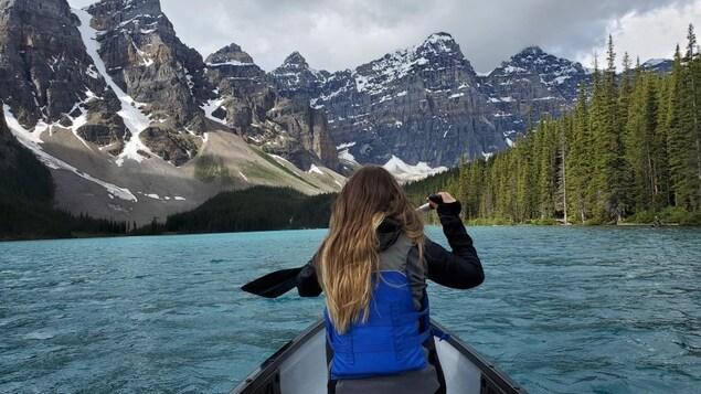 Une femme fait du canot sur le lac Moraine en Alberta.