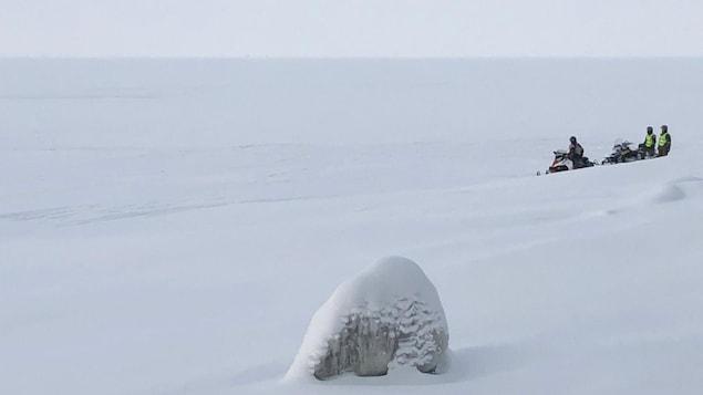 Des policiers à motoneige observent les glaces du lac Saint-Jean.