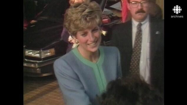 Lady Diana, souriante, serre la main à une personne, de dos