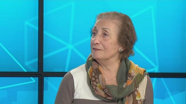 Une femme portant un foulard vert, brun et jaune devant des écrans bleus.
