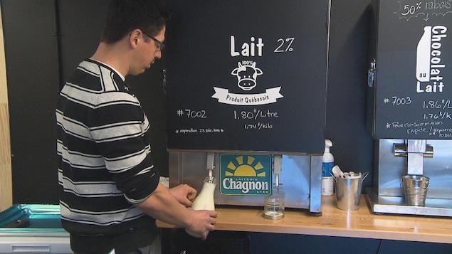 Un homme rempli une bouteille de verre avec du lait en fut.