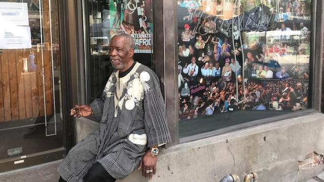 Un homme fume la cigarette alors qu'il est assis sur le rebord de la fenêtre d'un local commercial. Dans la vitrine sont présentées des photos de musiciens africains.