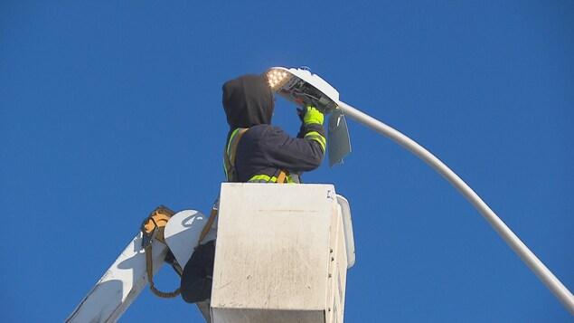 Un homme travaille sur un lampadaire.