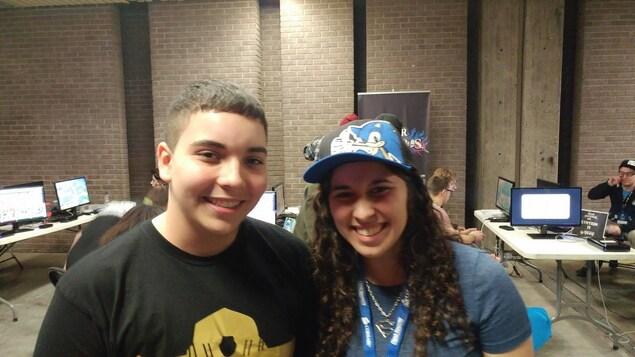Kelsy Medeiros et son frère Jayson Medeiros posent côte à côte, pendant que des joueurs s'adonnent à des jeux vidéo en arrière-plan.