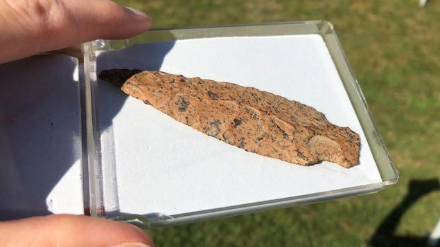 La lance, sculptée dans de la pierre orangée, est déposée dans un coffret de conservation.