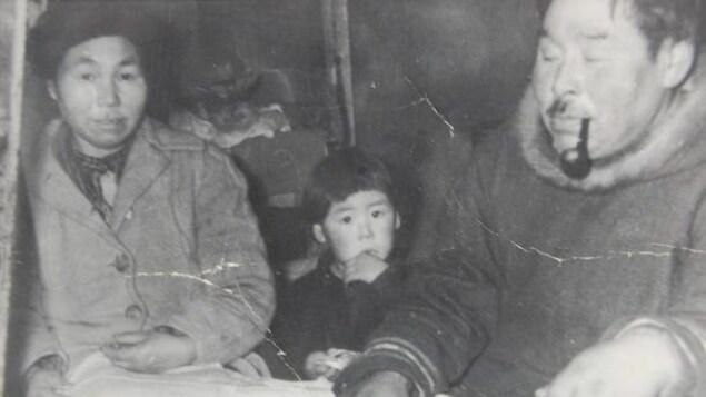 Un garçon inuit en compagnie de ses parents sur une vieille photo d'archive