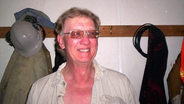 Larry Chroneyko souriant, avec un casque de travail derrière lui.