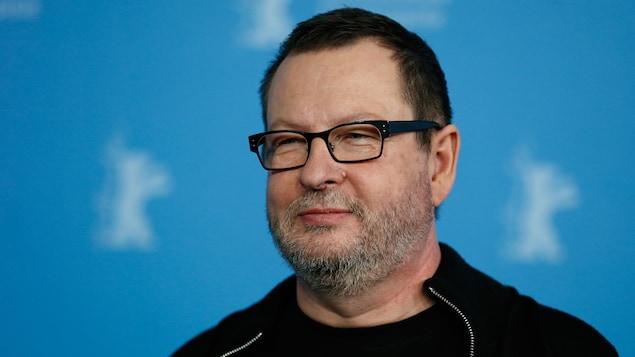 Portant une veste noire et des lunettes, le réalisateur danois Lars von Trier regarde sur le côté lors d'une séance photo au Festival international du film de Berlin, en 2014.