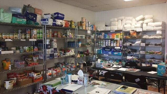 Les étagères de la banque alimentaire sont remplies de produits hygiéniques et d'aliments.