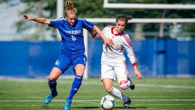 Sur le terrain, la joueuse de soccer Laura Chénard se dispute le ballon avec une adversaire.