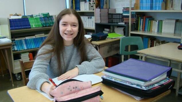 Laura Delisle assise à un pupitre dans une classe.