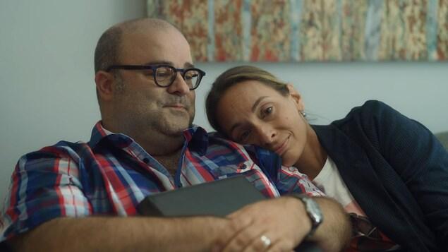 L'homme et la femme sont sur un divan et la femme met sa tête sur l'épaule de l'homme.