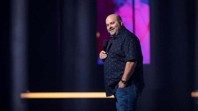 Laurent Paquin, qui porte une chemise foncée, est sur scène.