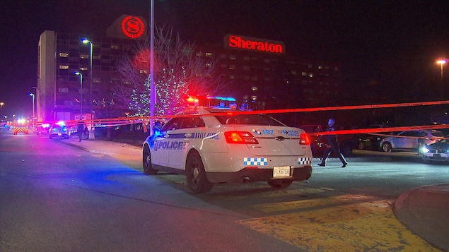 Une voiture de police est stationnée près d'un périmètre de sécurité à l'hôtel Sheraton.