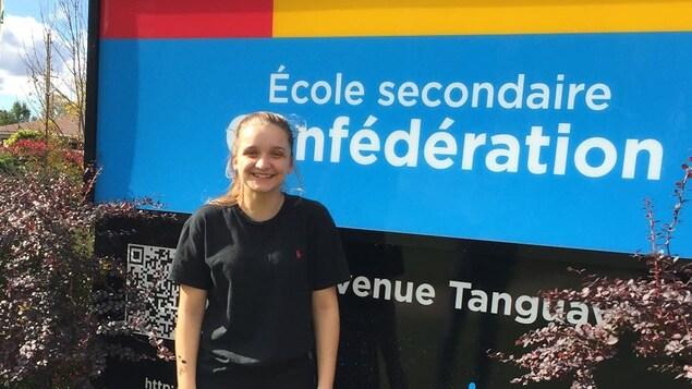 Photo de Laveena devant le panneau de l'école