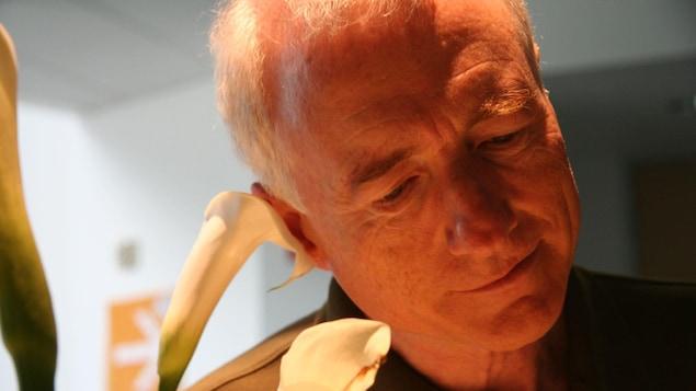 Un homme regarde des fleurs.