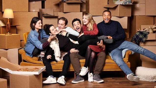 Les six jeunes adultes sont serrés les uns contre les autres sur un divan en riant.