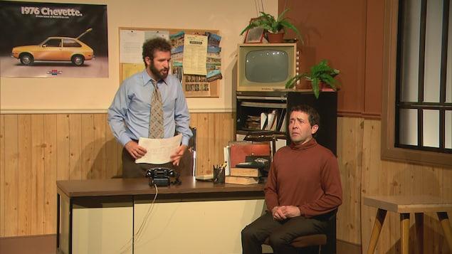 Deux comédiens jouent une scène dans un décor de bureau.