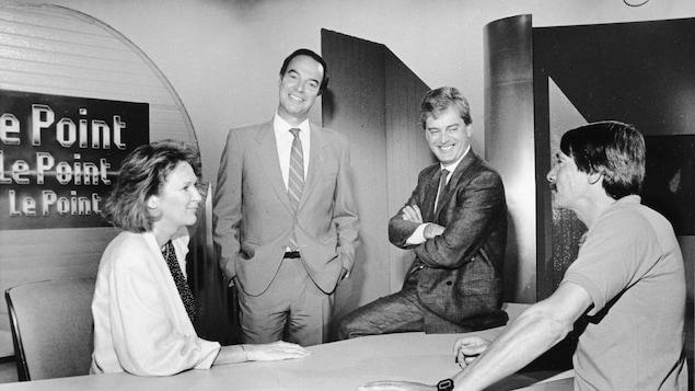 Madeleine Poulin, Pierre Nadeau, Simon Durivage et François Ayotte, qui discutent autour d'un bureau.