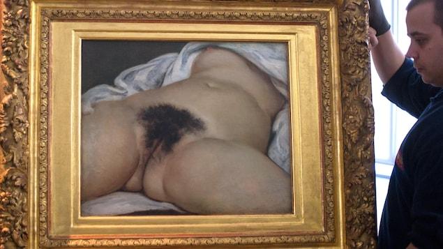 Un employé transporte le tableau représentant le tronc d'une femme nue, couchée sur le dos, les jambes écartées laissant voir son sexe.