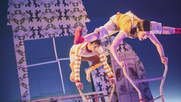 Deux danseurs jouent à saute-mouton sur une scène.