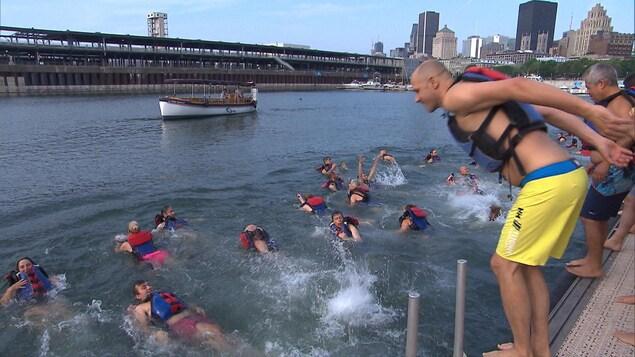 Un homme s'apprête à plonger du haut d'un quai dans le Vieux-Port.
