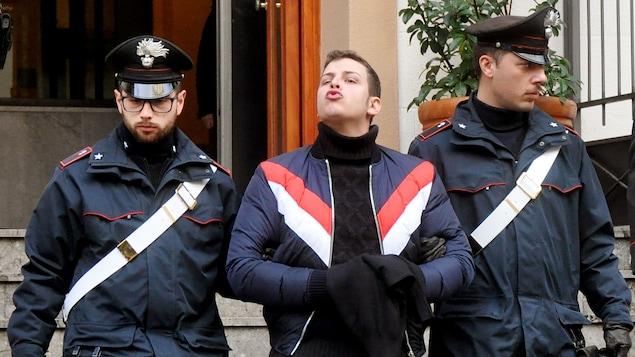 Un homme escorté par deux policiers envoie un baiser aux jounalistes.