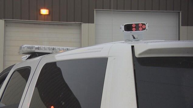 Un lecteur de plaques d'immatricuation automatique installé sur le toit d'une voiture.