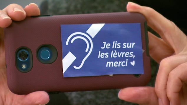 Un autocollant qui indique « Je lis sur les lèvres, merci » sur un téléphone cellulaire.