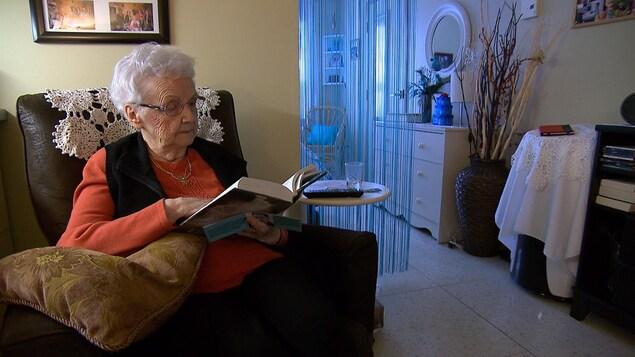 Une femme âgée est assise dans un fauteuil et lit un livre, Elle se trouve dans une chambre d'une résidence pour personnes âgées.