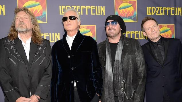 Quatre hommes se tiennent côte à côte sur un tapis rouge, prenant la pose pour les photographes.