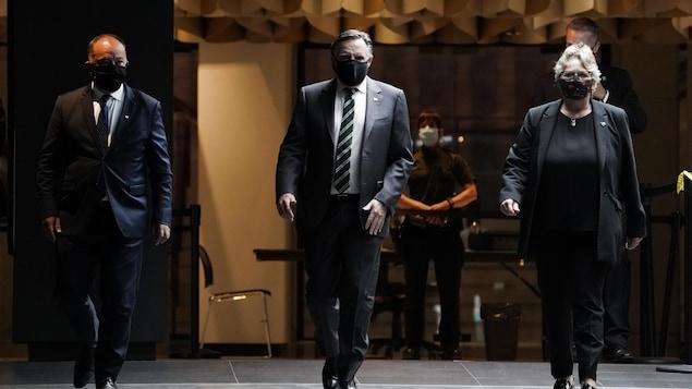 François Legault marche dans un couloir en compagnie de Christian Dubé et de Chantal Rouleau.
