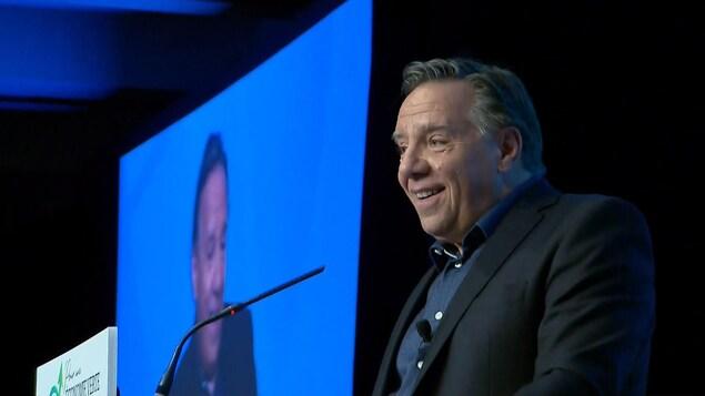 Un homme parle derrière un lutrin sur une scène avec un écran projetant son image derrière lui.