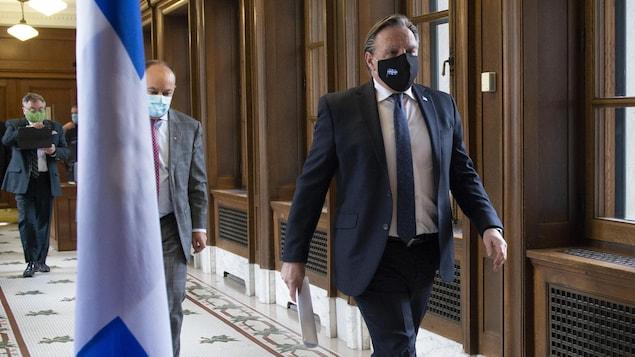 François Legault marche dans le couloir menant à la salle de conférence.