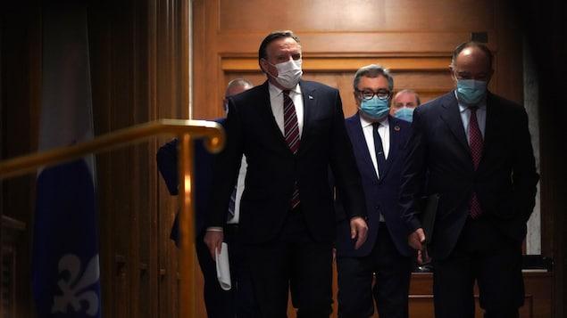 MM. Legault, Arruda et Dubé dans les corridors de l'Assemblée nationale.