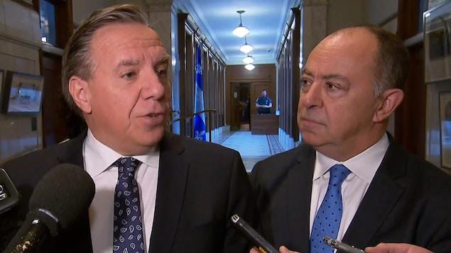 François Legault et Christian Dubé en mêlée de presse dans un corridor de l'Assemblée nationale.