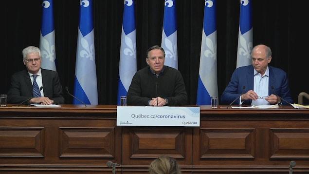 Le Dr Richard Massé, François Legault et Pierre Fitzgibbon en conférence de presse devant des drapeaux du Québec.