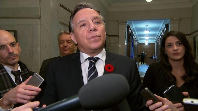 Plan rapproché de François Legault répondant à des questions de journalistes dans les couloirs de l'Assemblée nationale.