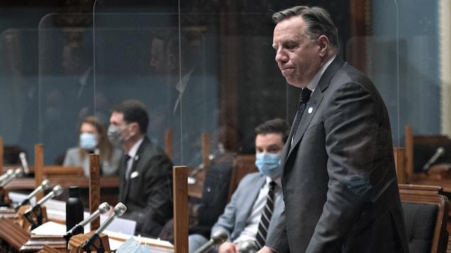 François Legault debout, l'air sérieux, à l'Assemblée nationale, avec en arrière-plan Simon Jolin-Barrette, assis, derrière un plexiglas.