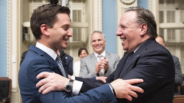 Le ministre de l'Immigration et leader parlementaire de la CAQ, Simon Jolin-Barrette, et le premier ministre François Legault se félicitent de l'adoption du PL 21, dimanche soir, au Salon bleu.