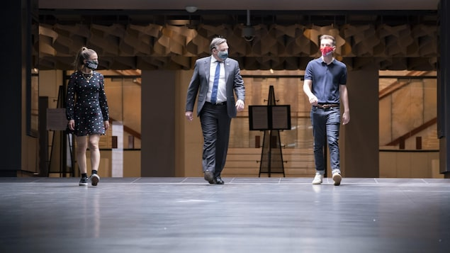Masqués, le premier ministre et les comédiens marchent dans les couloirs de la Place des Arts.