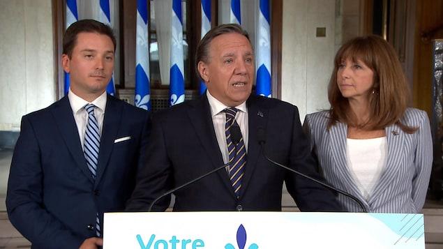 Le premier ministre Legault parle au micro en compagnie de Simon Jolin-Barrette et de Nathalie Roy.