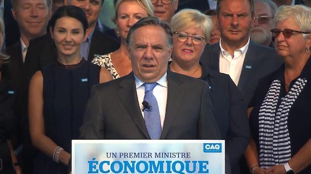 Un homme s'adresse à un auditoire derrière un lutrin sur lequel il est écrit: «Un premier ministre économique» avec le logo de la CAQ. D'autres personnes sont debout derrière lui.
