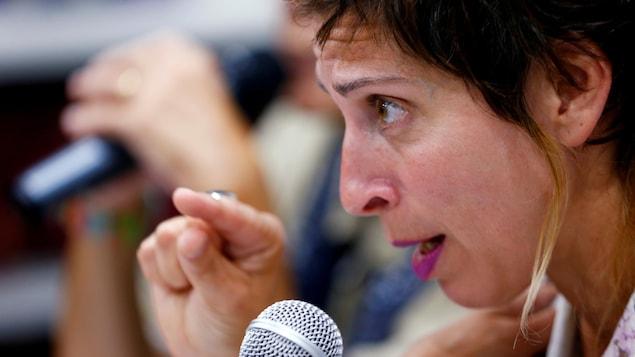 Une femme parle dans un micro, on la voit de profil.